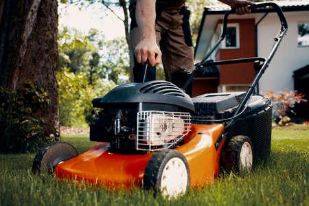 Closeup of professional gardener turning on the lawn mower Stok Fotoğraf