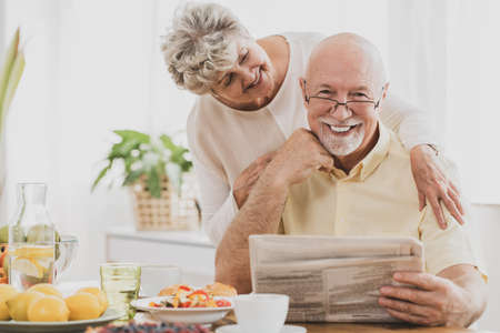 Adorable senior couple at home reading newspaper together at breakfast table