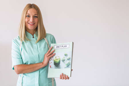 Young beautiful dietitian holding a diet plan, copy space on the empty white wall Stok Fotoğraf