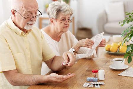 Senior couple sitting at dining table taking medicines Stok Fotoğraf