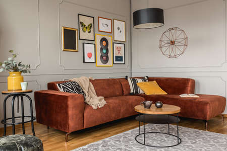 Gallery of trendy posters in elegant gray living room interior with brown corner sofa