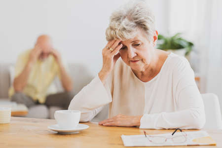 Senior woman with headache sitting at dining table drinking coffee