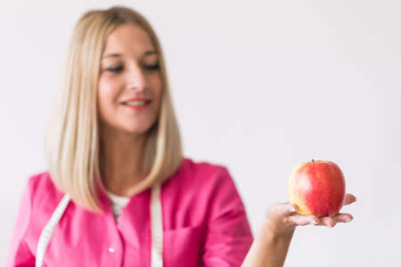Young beautiful dietitian is standing in the office holding an apple Stok Fotoğraf