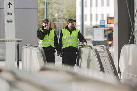 Two policeman in reflective jackets talking by walkie-talkie patrolling the city center Stok Fotoğraf