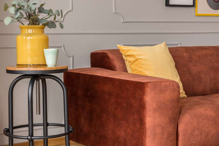 Yellow vase on tall side table in trendy living room interior with brown sofa and gray wall