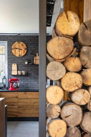 Wooden clock on black brick wall in trendy kitchen with red kitchen robot Stok Fotoğraf