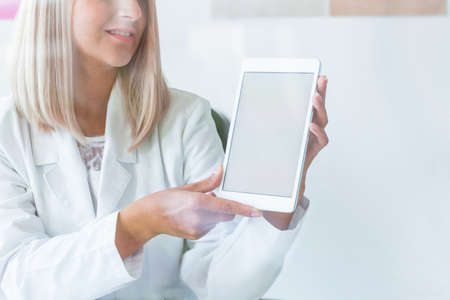 Pretty blonde nurse in medical uniform with tablet, copy space on empty white wall