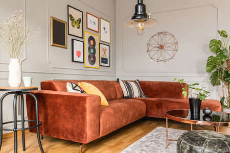 Stylish living room interior with comfortable couch, coffee table, flowers and posters