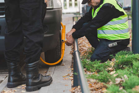 Close-up of policeman setting a wheel clamp on a car parked by the pavement