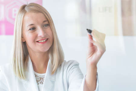 Young blond dietitian holds a marker and writes on a glass board
