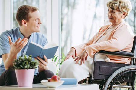 Young male caregiver keeping the company to an older woman on wheelchair