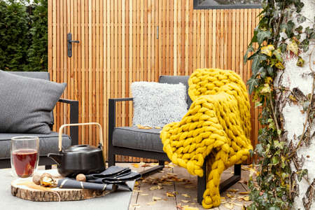 Cozy garden with gray armchairs, yellow blanket and kettle and glass on the table Stok Fotoğraf