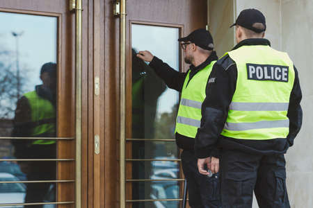 Police officers on duty, knocking on the doors of the suspect