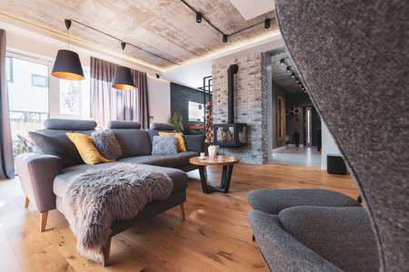 Gray couch with pillows next to modern fireplace in stylish living room interior Stok Fotoğraf