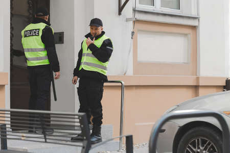 Two policemen in uniforms and with walkie-talkie standing in front of police office