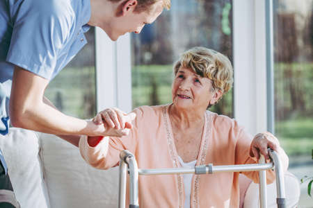 Elderly disabled woman trying to walk with nurse's help