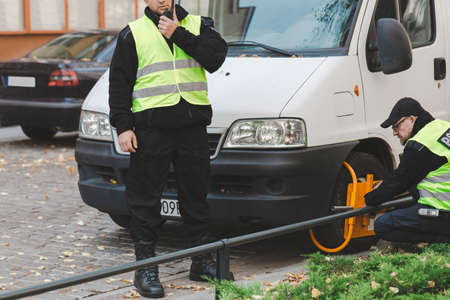 Two policeman setting a wheel clamp on a wrong parked car