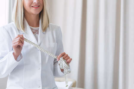 Young blond-haired dietitian in white uniform holding a tailor centimeter