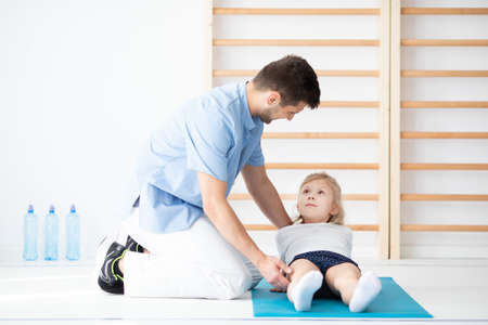 Young physical therapist exercising with a girl with spine problems Stock Photo