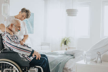 Senior man with oxygen mask sitting on a wheelchair supported by his wife Stock Photo