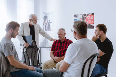 Older psychologist helping his patient during group psychotherapy Stock Photo
