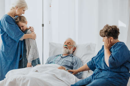 Senior sick man dying in hospital bed Stock Photo