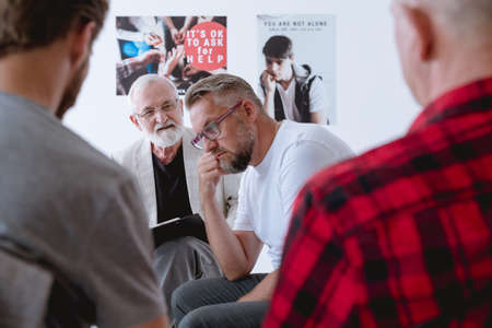 Worried older man on a session of group psychotherapy Stock Photo
