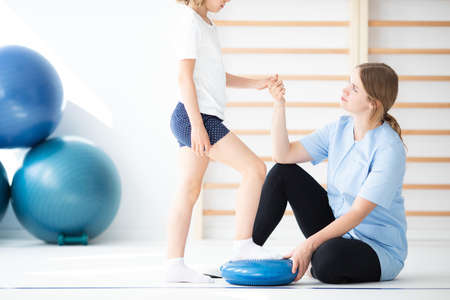 Young physiotherapist exercising with little patient on a sensory cushion