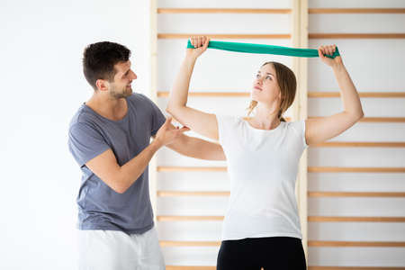Male physiotherapist helping young girl with exercise with stretching the band Stock Photo