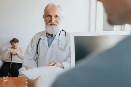Senior caring doctor taking patient's card from the registration desk Stock Photo