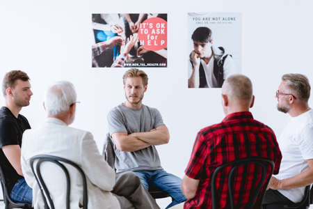 Group of men talking about emotions on a session of therapy Stock Photo