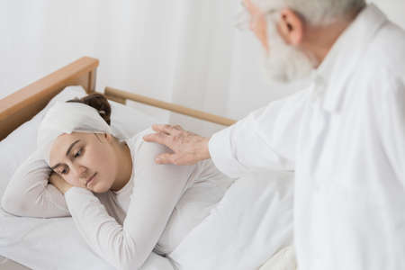 Senior caring doctor checking young female patient's health Stock Photo