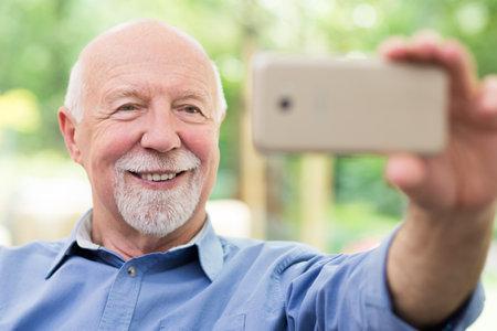 Older man taking a selfie on the park