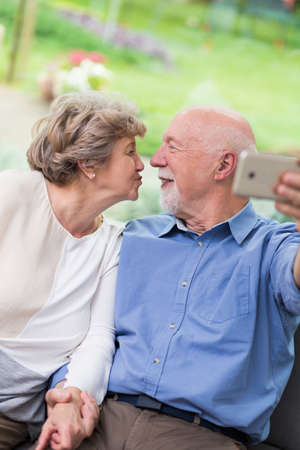 Older married couple kissing for a picture Stock Photo