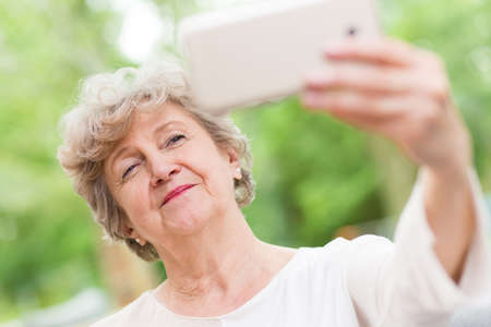 Senior smiling woman taking a picture of herself with her smartphone