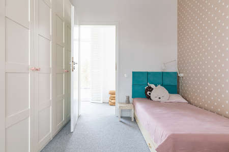 Cute scandinavian style kid's bedroom with single bed