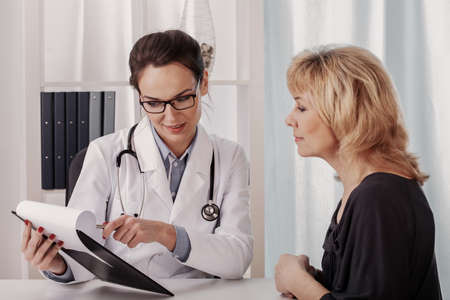 Young beautiful female doctor showing medical records to her senior patient