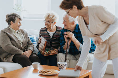 Helpful nurse serving the dessert to older people Stock Photo