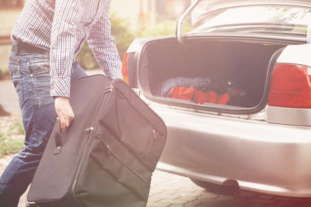 Man holding big suitcase in front of open car trunk Stock Photo