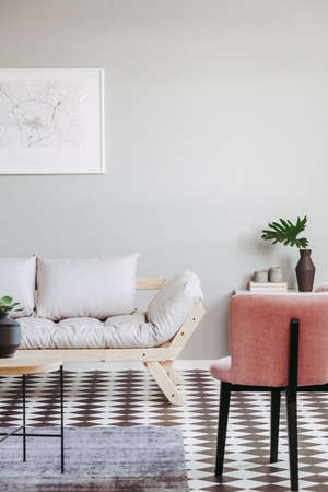 Pastel pink armchair and beige scandinavian futon in trendy living room interior with black and white floor