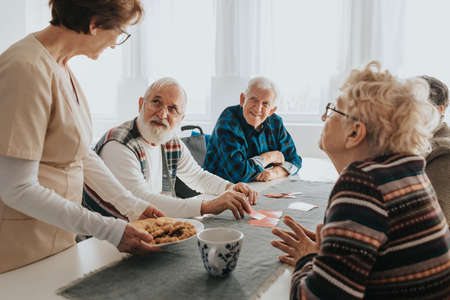 Helpful caregiver serving the snacks to the group of older people in nursing home Stock Photo