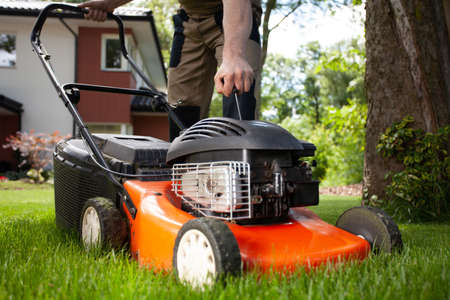 Closeup of professional gardener turning on the lawn mower Stock Photo