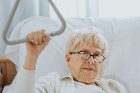 Sick older woman trying to stand up using a handle Stock Photo