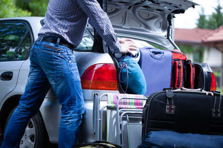 Man trying to fit all his suitcases into car trunk