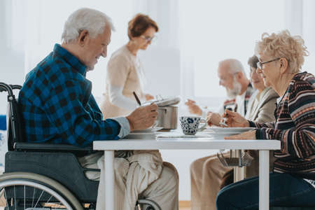 Group of senior people in day-care center eating the dinner together Stock Photo