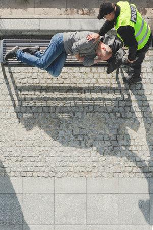 Police officer wake ups homeless man lying on the bench in the city Reklamní fotografie