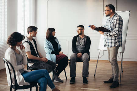 Handsome senior professional therapist stands in front of a group of people of different ages during meeting for people with social problems