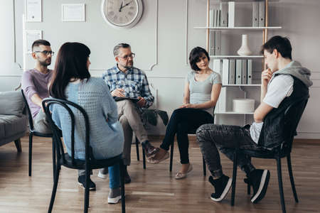 Group of people of different ages sits in a circle during a meeting with a professional therapist Stock fotó
