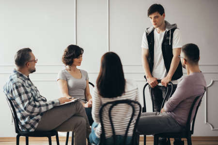 Sad teenager stands in front of a group of people of different ages during a therapy group meeting and talks about his problems Stock fotó