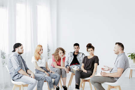 Group of teenagers during psychotherapy with professional counselor, copy space on empty white wall